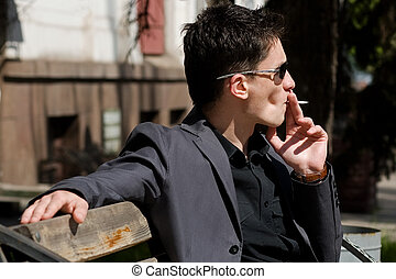 Man smoking a cigarette sitting on a bench