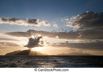 Sunrays breaking through the clouds over the sea and islands