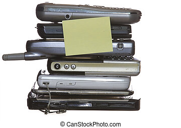 Mobile phones stacked with blank yellow note in a white...