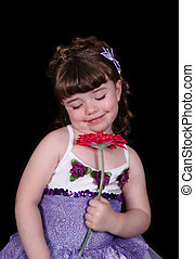 little girl with eyes closed in tutu smelling flower...