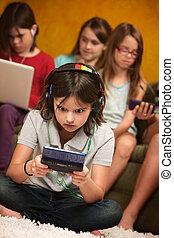 Little Girl Engrossed In Gaming - Little Caucasian girl...
