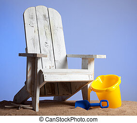 White adirondack chair with shovel and pail on sand with a...