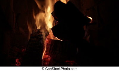 Adjusting firewood in fireplace, closeup shot.