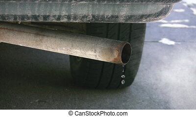 Car exhaust. - A car exhaust drips and blows vapour.