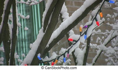 Snowy Christmas lights. - Snow falls on outdoor Christmas...