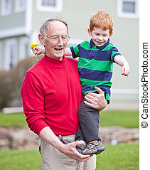 Grandfather and grandson - Grandfather carrying redheaded...