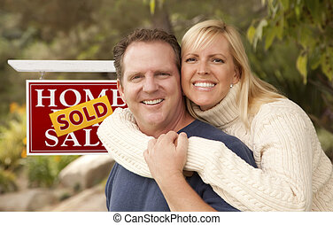 Happy Couple in Front of Sold Real Estate Sign - Happy...