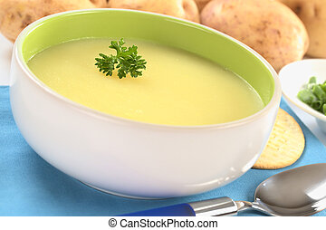 Fresh potato cream soup garnished with a parsley leaf with...