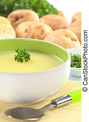 Fresh potato cream soup garnished with a parsley leaf with green onion, baguette slices, raw potatoes and parsley in the back (Selective Focus, Focus on the parsley leaf in the bowl)