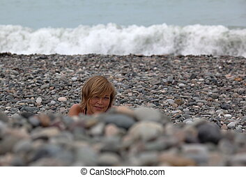 Smiling lady on pebbles beach. - Smiling lady sunbathing on...
