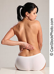 Massage lower back pain for semi nude young woman - Lower...