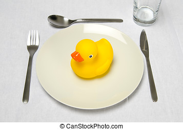 Rubber duck on plate setting - A rubber duck sitting on a...