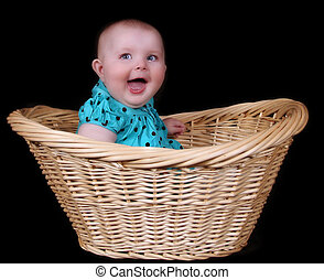 sweet baby girl sitting in wicker basket. isolated