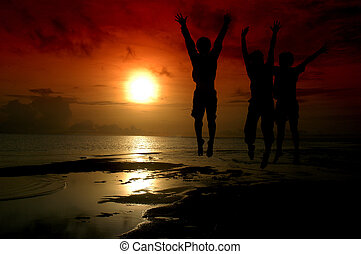 silhouette of three people jumped into the rising sun