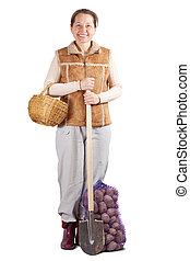 Happy  woman  with spade and potatoes
