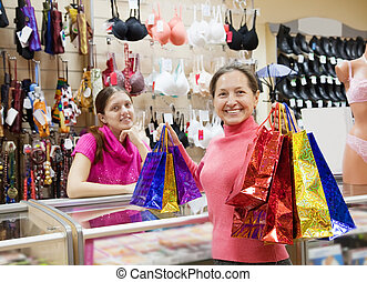 Buyer with purchases at counter - Buyer and salesman with...