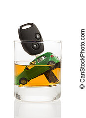 Car keys and glass with alcohol - Car keys and a jar of...