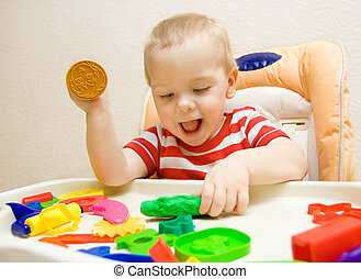 happy child playing plasticine - happy smiling child playing...