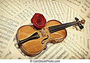 old violin with musical notes and rose