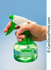 Hand holding water sprayer - Hand holding green water...