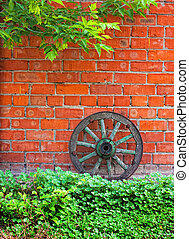 old wagon wheel against the brick wall