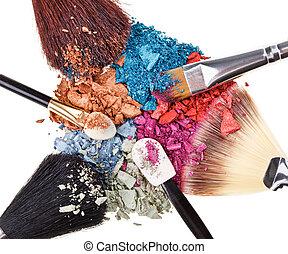 Composition with makeup brushes and broken multicolor eye...