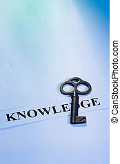 Key to Knowledge - A key laying on a piece of paper with the...