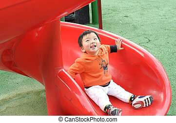 baby playing on sliding board in a children's playground
