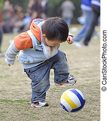baby playing football in a park