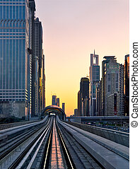 sunset at Dubai, UAE - Modern city at sunset, metro overpass...