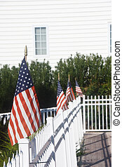 American Flags on White Picket Fence - A row of american...