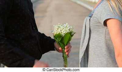lily of valley - man presents a woman bouquet lily of the...