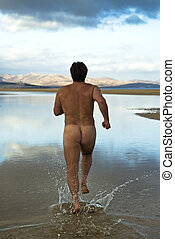 Naked man running in water - A naked man running through...