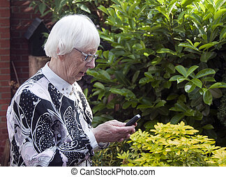 grandmother make sms - grandmother with mobile phone making...