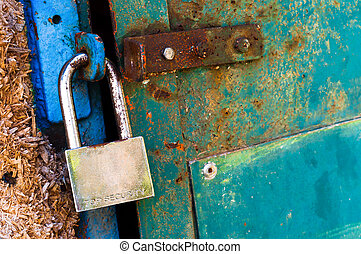 Rusty old padlock on metal door