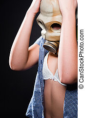 Girl wearing gasmask and white lingerie holding her head