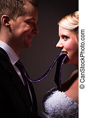 Beautiful young bride holding her groom on a leash