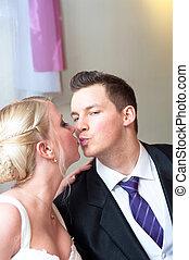 Handsome groom kissing her bride