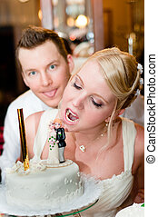 Young bride is going to bite her cake with groom in background