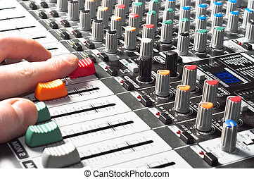 Closeup of an audio sound mixer with the hand of a man