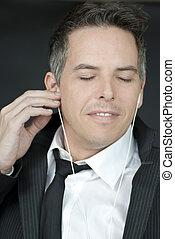 Confident Businessman Puts In Headphones