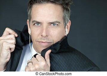 Close-up of a confident businessman wearing headphones looking to camera while he adjusts his jacket.