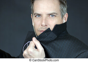 Close-up of a confident businessman wearing headphones looking to camera while he adjusts his suit.