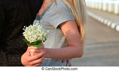 loving couple embracing on the street holding a bouquet of...