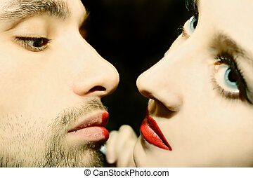 Kiss macro - Kiss of young men and women with bright red...