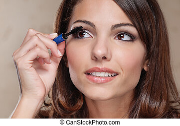 Woman applying mascara on her eyelashes - Attractive young...
