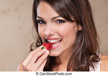 Pretty young woman eating a strawberry - Portrait of pretty...