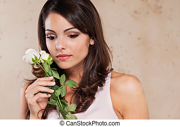 Pretty young woman holding a white rose