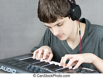 Focused Teen Plays Keyboard - Close-up of a focused teen...