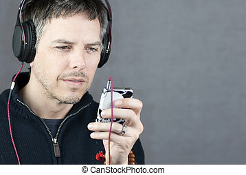 Headphone Wearing Man Looks At MP3 Player - Close-up of a...